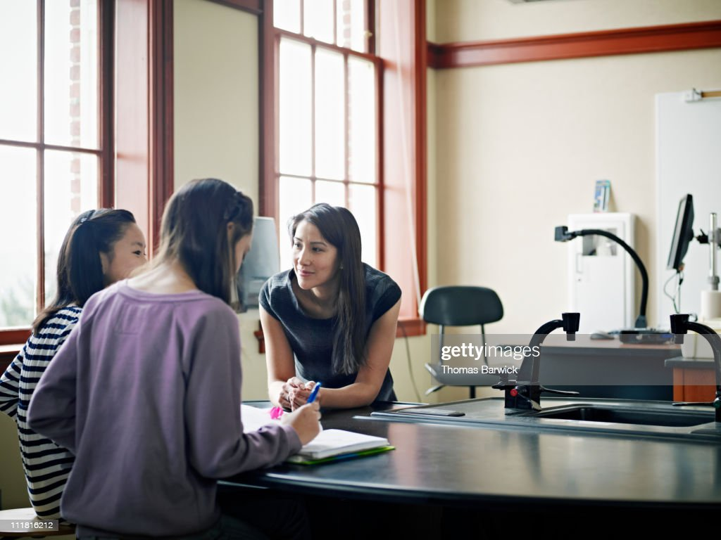 Teacher working with two students in classroom : Stock Photo