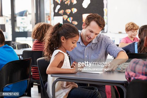 Teacher working with young schoolgirl at her desk in class : Stock Photo