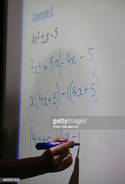A teacher writes an equation on a whiteboard during a maths lesson at a secondary school on December 1 2014 in London England Education funding is...