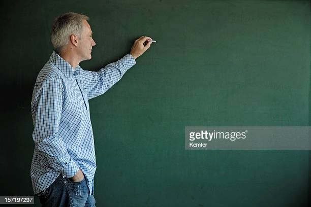 teacher writing at blackboard