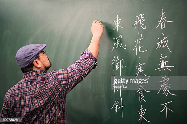 Teacher writing Chinese poem on board