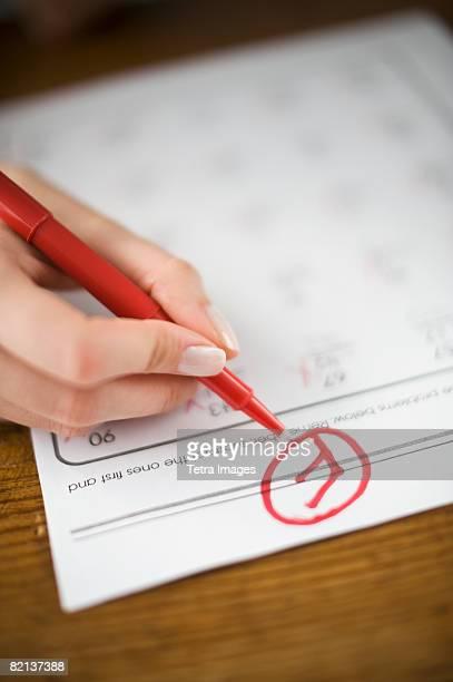 Teacher writing F grade on worksheet
