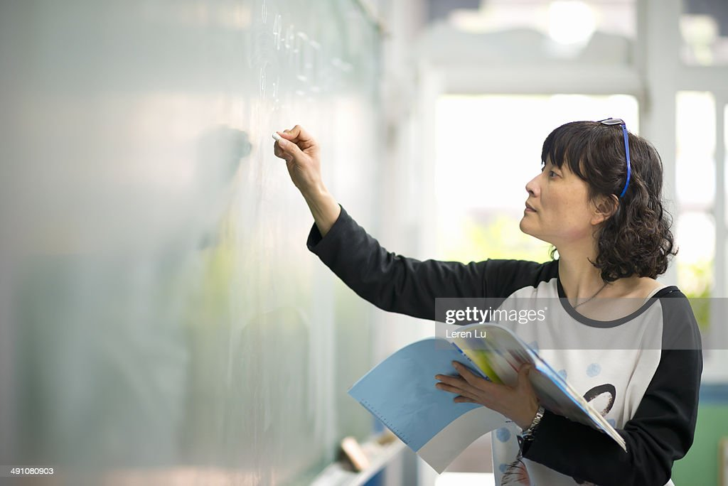Teacher writing on chalkboard : Stock Photo