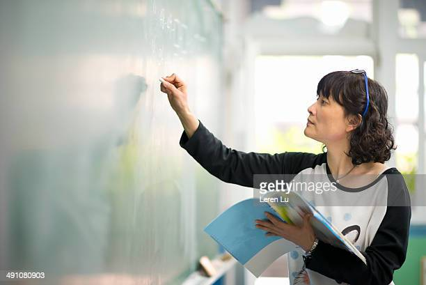 Teacher writing on chalkboard
