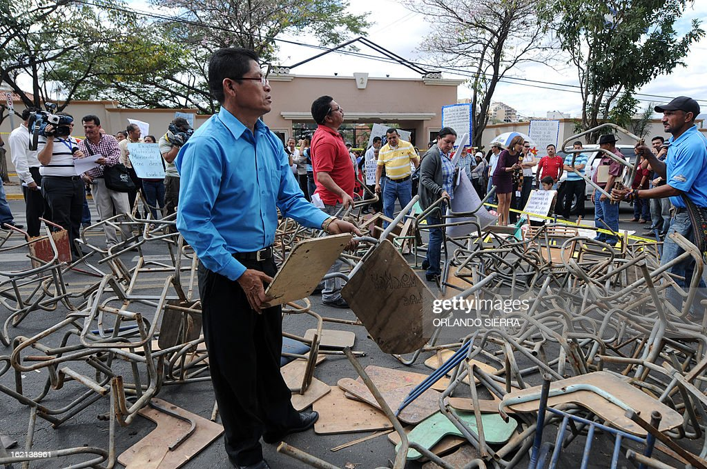 Teachers and schoolchildren parents place broken desks on the Juan Pablo II boulevard which goes past the Government House, during a protest against Porfirio Lobo's government demanding their salaries pay and better infrastructure, in Tegucigalpa, on February 19, 2013. AFP PHOTO/Orlando SIERRA