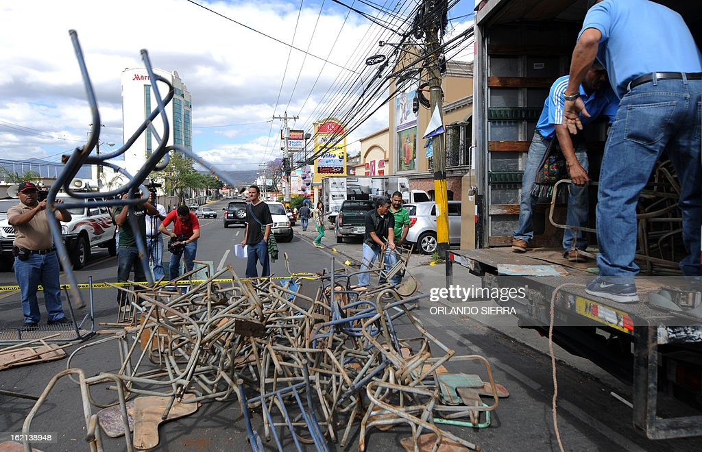Teachers and schoolchildren parents unload broken desks to the Juan Pablo II boulevard which goes past the Government House, during a protest against Porfirio Lobo's government demanding their salaries pay and better infrastructure, in Tegucigalpa, on February 19, 2013. AFP PHOTO/Orlando SIERRA