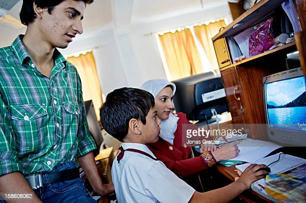 Teachers are teaching a student about computers at the New Era Public School in Srinagar During the years of conflict schools were closed As the...