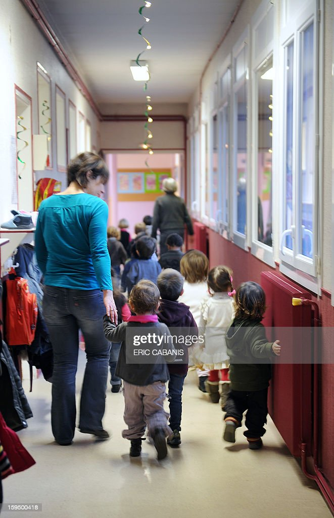 Teachers assistant Audrey Bras (L) takes care of two-year-old children at a kindergarten in Firmi, central southern France, on January 14, 2013. French government is expected to announce in the coming days schooling for toddlers (children less than three years). AFP PHOTO / ERIC CABANIS CAPTION