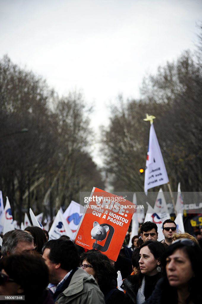 Teachers attend a demonstration against government austerity measures organized by the Portuguese Teachers National Front Union (FENPROF) in Lisbon, on January 26, 2013. Placard reads 'Those who have created the crisis, shoud pay for it.' AFP PHOTO / PATRICIA DE MELO MOREIRA