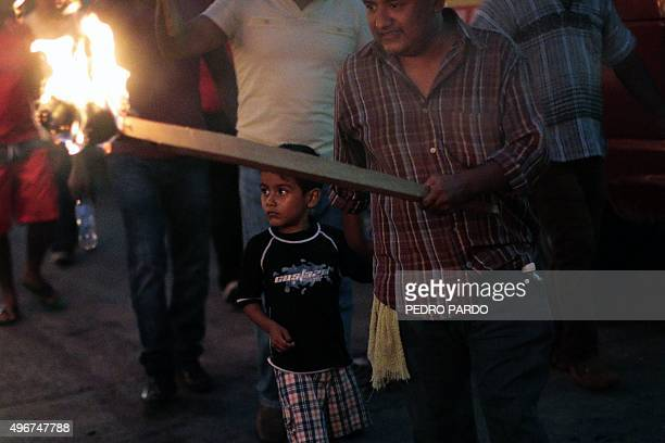 Teachers carry torches during a demonstration against insecurity in Acapulco in the Mexican state of Guerrero on November 11 2015 Acapulco once known...