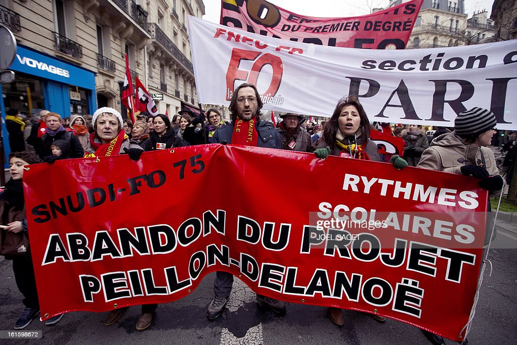 Teachers hold a banner reading 'Abandonment of the (French Education Minister) Peillon's and (Paris Mayor) Delanoe's project' as they demonstrate on February 12, 2013 in Paris, as part of a nationwide strike day over the government's plans to make children attend classes five days a week, instead of the current four. The government recently issued a decree introducing a half day of school on Wednesdays for children 3 to 11 starting in September, while reducing the school day by 45 minutes the rest of the week.