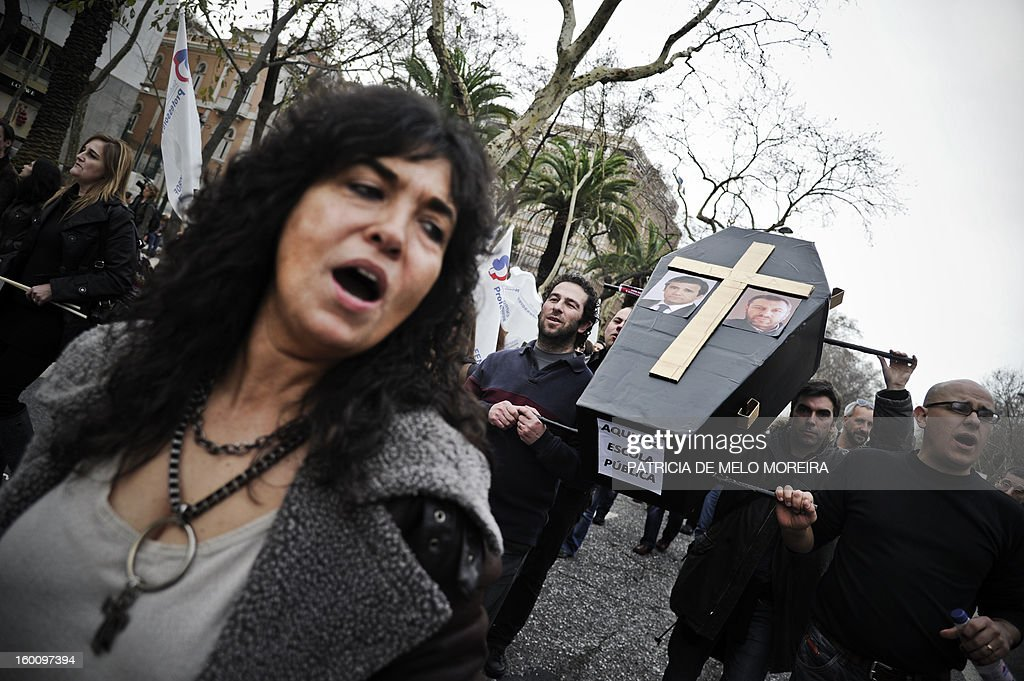 Teachers hold a coffin displaying pictures of Portuguese Prime Minister Pedro Passos Coelho and Portuguese Education Minister Nuno Crato pictures and reading 'Here lies the public school' during a demonstration against government austerity measures in education organized by the Portuguese Teachers National Front Union (FENPROF) in Lisbon, on January 26, 2013.