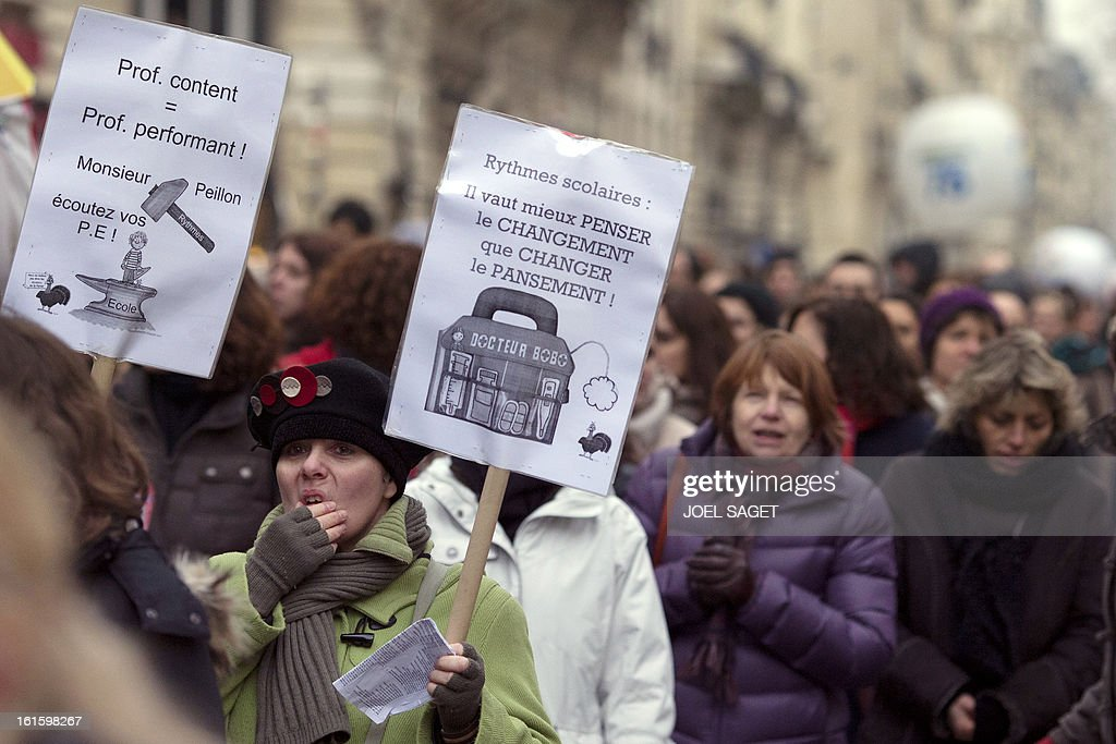 Teachers hold placards as they demonstrate on February 12, 2013 in Paris, as part of a nationwide strike day over the government's plans to make children attend classes five days a week, instead of the current four. The government recently issued a decree introducing a half day of school on Wednesdays for children 3 to 11 starting in September, while reducing the school day by 45 minutes the rest of the week.