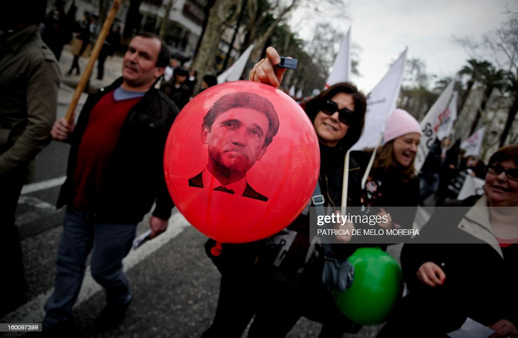 A teachers holds a ballon depecting a picture of Portuguese Prime Minister Pedro Passos Coelho during a demonstration organized by the Portuguese Teachers National Front Union (FENPROF) against government austerity measures in education in Lisbon, on January 26, 2013.