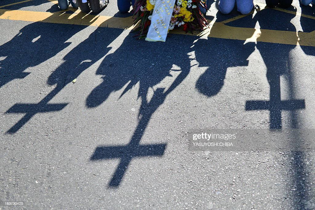 Teachers knee on the ground as they hold crosses representing the death of education during a protest demanding better working conditions in Rio de Janeiro, Brazil, on October 9, 2013.