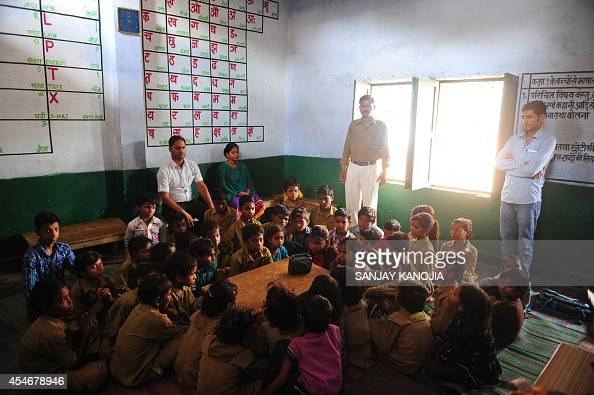 Teachers look on as Indian schoolchildren crowd around a radio as they listen to a broadcast by Indian Prime Minister Narendra Modi delivering his...