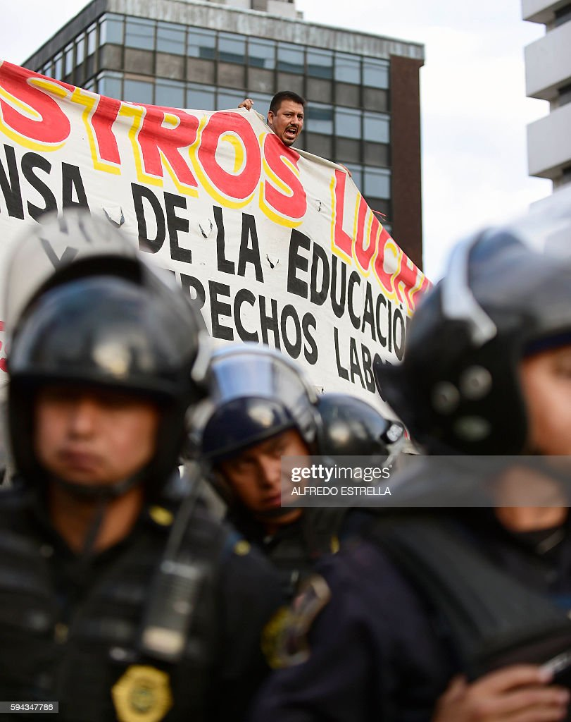 Teachers on strike and locals hold a banner behind a line of police during a protest against the education reform in Mexico City on August 22 2016...