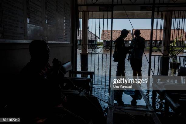 Teachers prepare for fishing at a yard of school that is mostly submerged by rising sea levels on June 6 2017 in Pekalongan Indonesia Indonesia is...