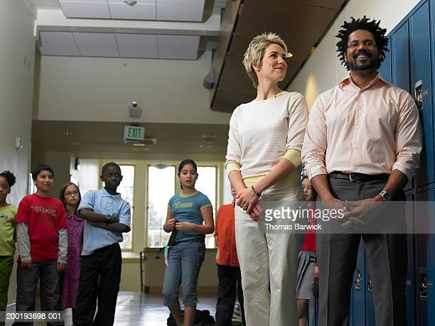 Teachers standing in hallway filled with students