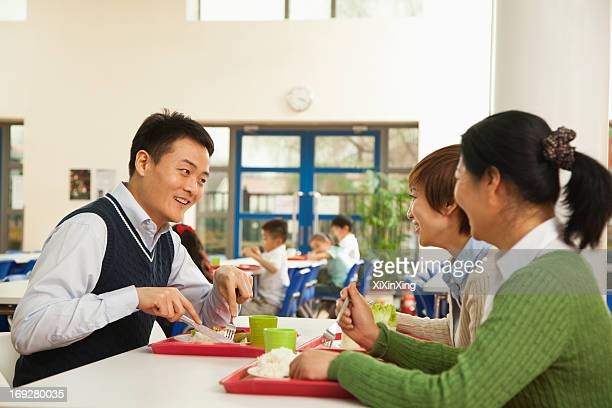 Teachers talking at lunch in school cafeteria