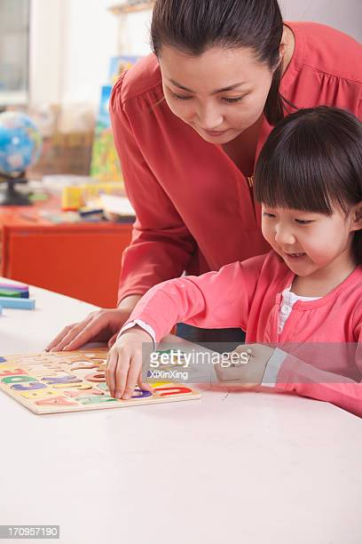Teaching Helping Young Girl with Cut-Out Alphabet Letters