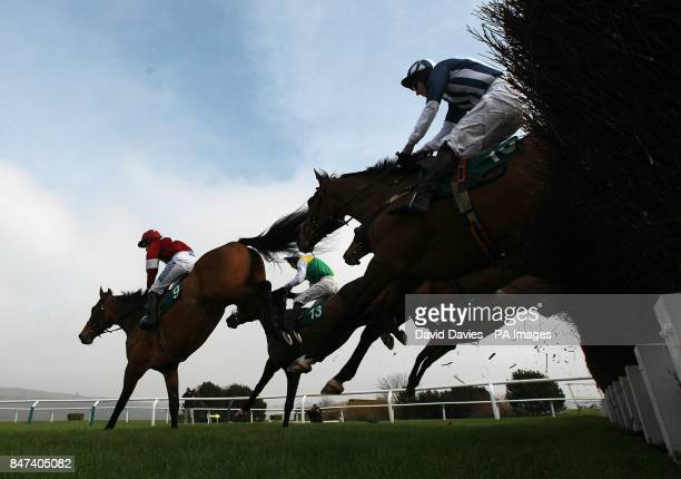 Teaforthree ridden by J T McNamara clears a fence behind Four Commanders ridden by Nina Carberry during the Diamond Jubilee National Hunt Chase on...