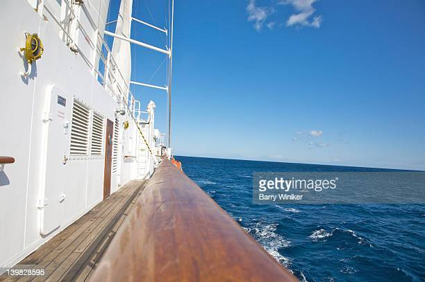 Teak railing separating the whitewashed Wind Spirit of Windstar Cruises from the blue waters of the Mediterranean Sea
