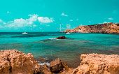 Teal and orange mood of Cala Tarida Beach and beautiful mediterranean coastline in Ibiza island, part of Balearic archipelago in Spain.