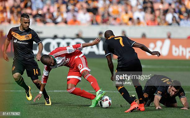 Teal Bunbury of New England Revolution attempts to maintain control of the ball as dribbles between DaMarcus Beasley of Houston Dynamo Alex and Will...