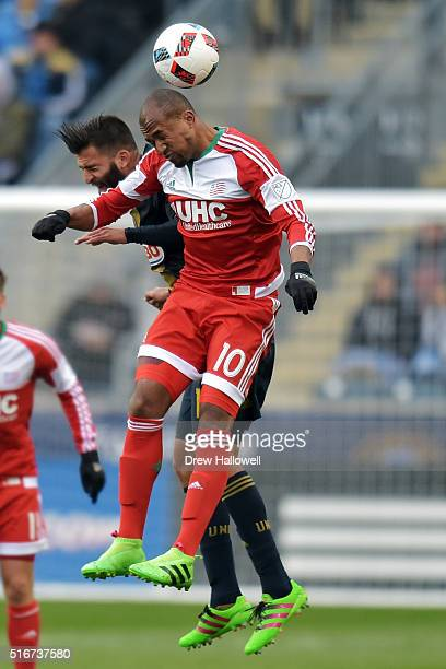 Teal Bunbury of New England Revolution heads the ball away from Richie Marquez of Philadelphia Union at Talen Energy Stadium on March 20 2016 in...