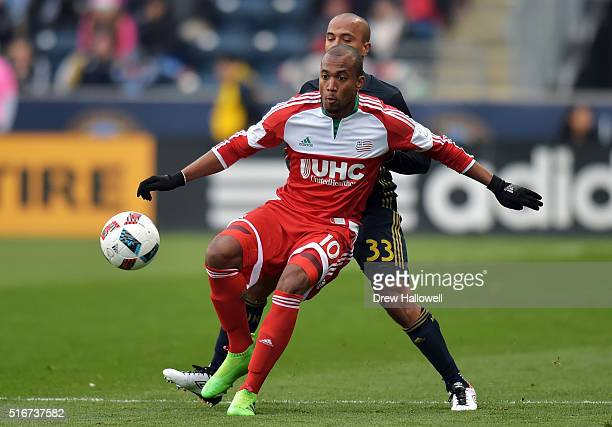 Teal Bunbury of New England Revolution plays the ball while holding off Fabinho of Philadelphia Union at Talen Energy Stadium on March 20 2016 in...