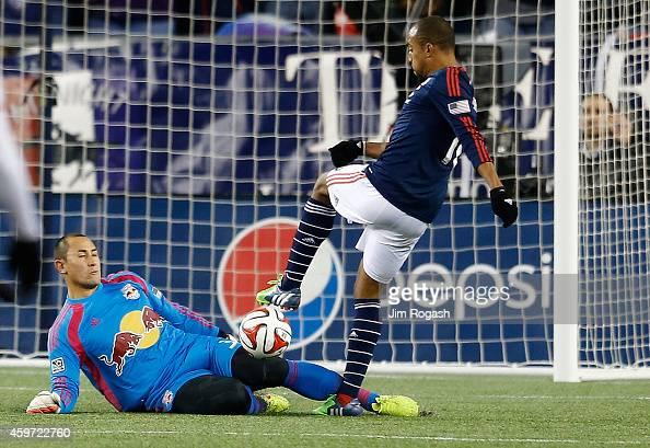 Teal Bunbury of New England Revolution shoots on net as Luis Robles of New York Red Bulls defends during the second half of Leg 2 of the MLS Eastern...