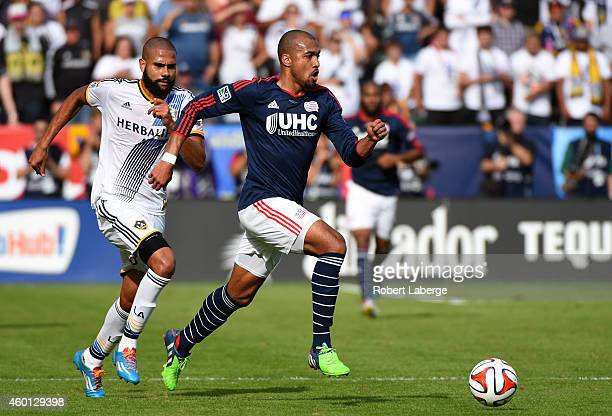 Teal Bunbury of the the New England Revolution runs with the ball as Leonardo of the Los Angeles Galaxy tries to catch him during the 2014 MLS Cup...