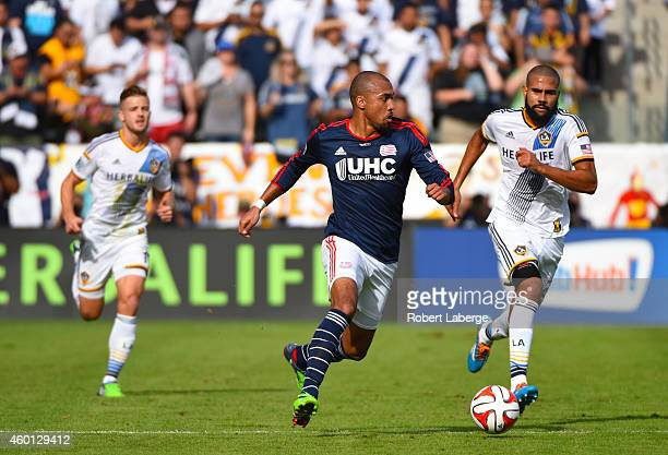 Teal Bunbury of the the New England Revolution runs with the ball as Leonardo of the Los Angeles Galaxy tries to catch him and Robbie Rogers looks on...