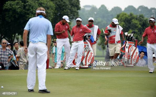 Team Asia look on at Victor Dubuisson of Team Europe misses his putt on the 16th green during the foursome matches on day two of the EurAsia Cup at...