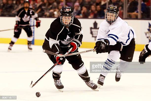 TORONTO ON JANUARY 23 Team Black forward Hayley Wickenheiser is checked by Team White Tara Watchorn during second period play at the Canadian Women's...