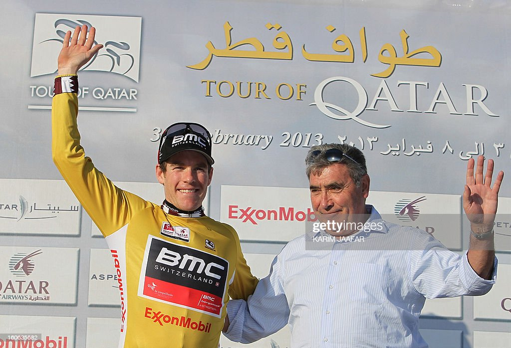 US team BMC's cyclist Brent Bookwalter celebrates on the podium with the overall leader's Gold jersey that he received from Belgian cycling legend Eddy Merckx (R) after BMC won the second stage of the 2013 cycling Tour of Qatar, a 14-kilometre team time-trial, in the Qatari capital Doha, on February 4, 2013. The BMC's win means that Bookwalter keeps the leader's golden jersey in the overall classification, ahead of his compatriot Taylor Phinney and Britain's Adam Blythe.