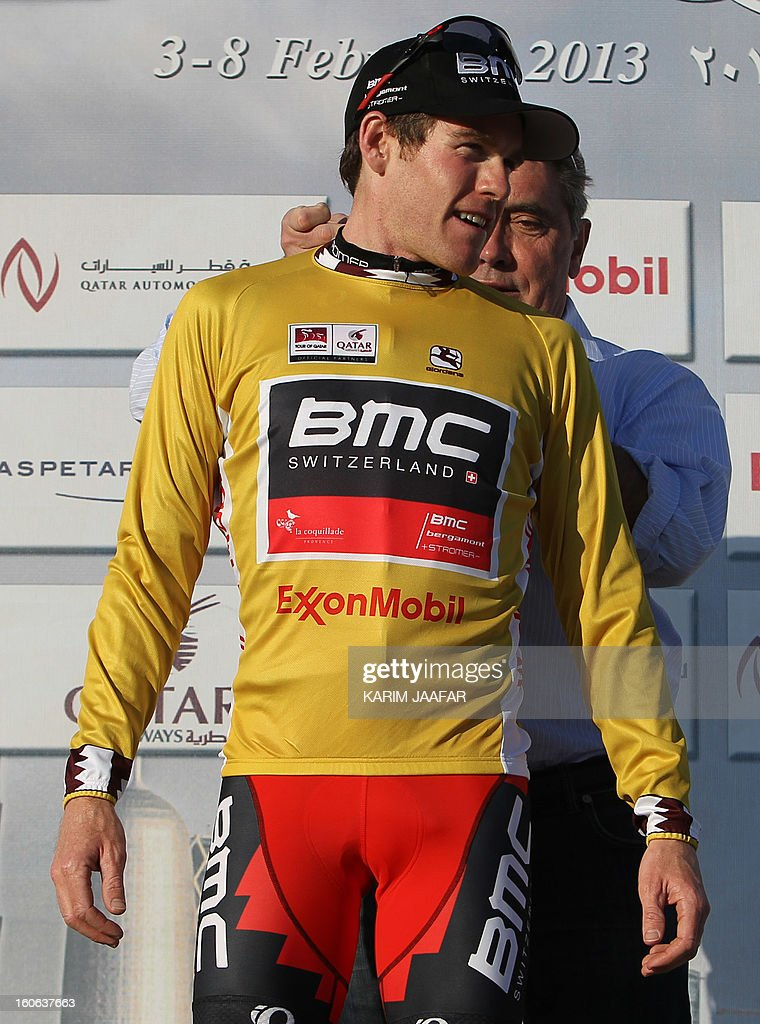 US team BMC's cyclist Brent Bookwalter receives the overall leader's Gold jersey from Belgian cycling legend Eddy Merckx (R) on the podium after BMC won the second stage of the 2013 cycling Tour of Qatar, a 14-kilometre team time-trial, in the Qatari capital Doha, on February 4, 2013. BMC's win means that Bookwalter keeps the leader's golden jersey in the overall classification, ahead of his compatriot Taylor Phinney and Britain's Adam Blythe. AFP PHOTO / AL-WATAN DOHA / KARIM JAAFAR == QATAR OUT ==