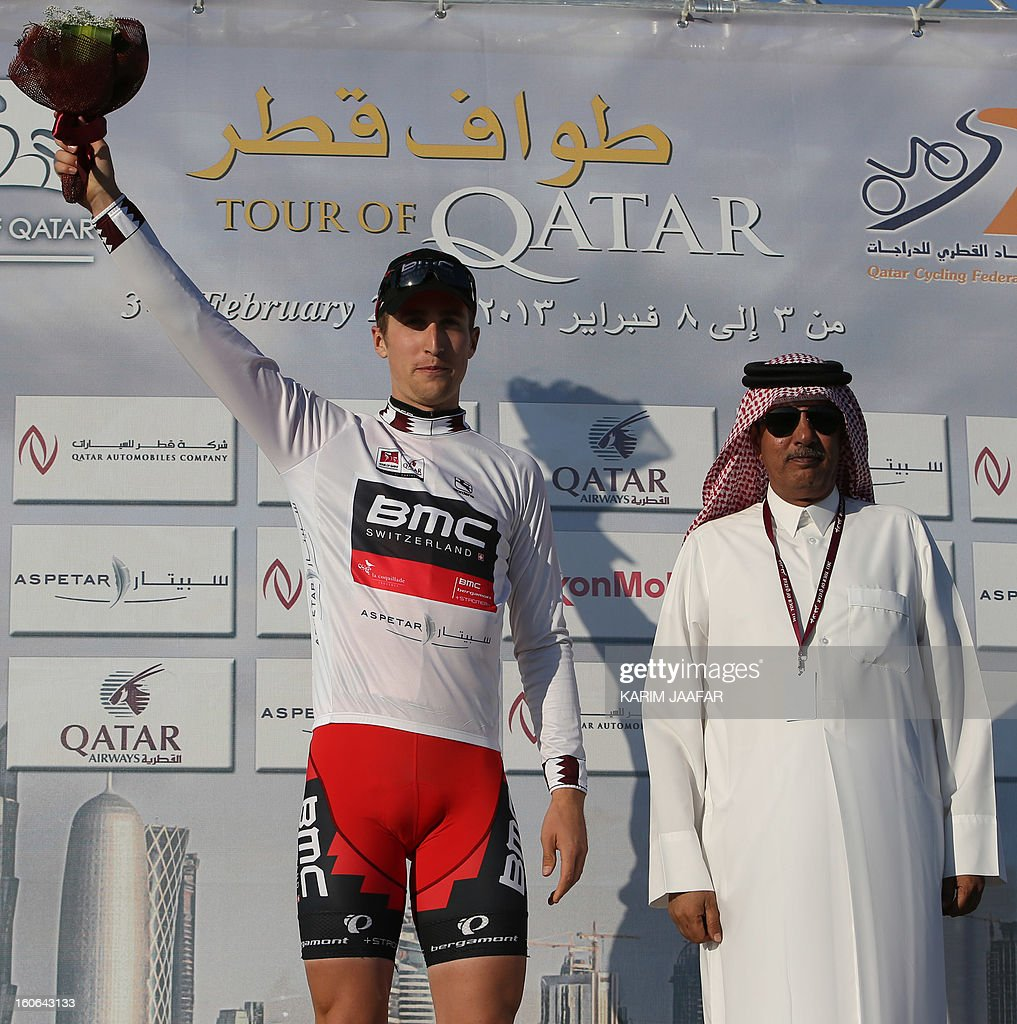 US team BMC's leader Taylor Phinney celebrates on the podium after receiving the Best Young White jersey at the end of the second stage of the 2013 cycling Tour of Qatar, a 14-kilometre team time-trial, in the Qatari capital Doha, on February 4, 2013. BMC won the event in 16min 7.21sec, five seconds ahead of Britain's Team Sky and 10 seconds in front of Omega Pharma. AFP PHOTO / AL-WATAN DOHA / KARIM JAAFAR == QATAR OUT ==