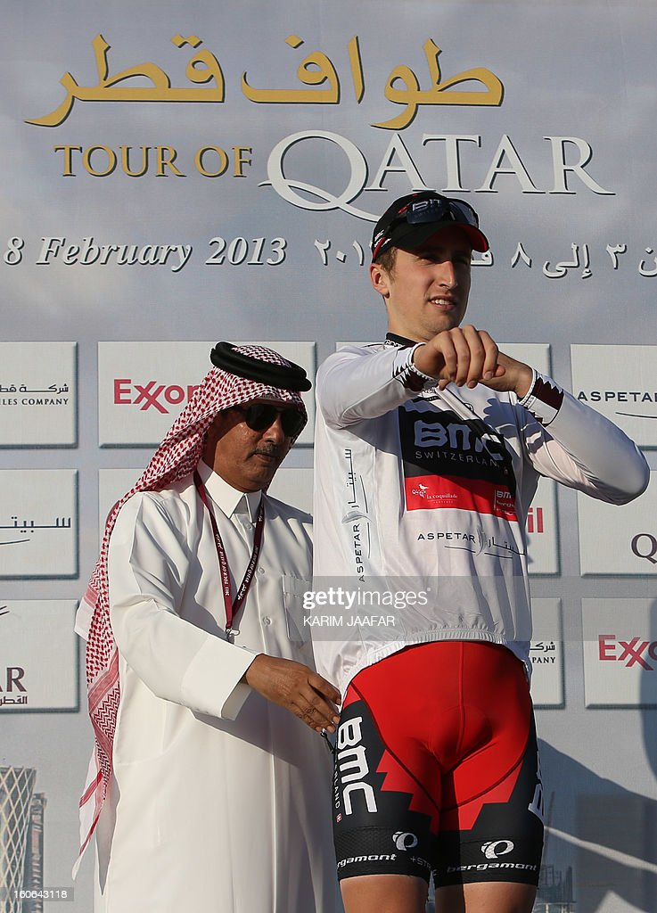 US team BMC's leader Taylor Phinney receives the Best Young White jersey on the podium at the end of the second stage of the 2013 cycling Tour of Qatar, a 14-kilometre team time-trial, in the Qatari capital Doha, on February 4, 2013. BMC won the event in 16min 7.21sec, five seconds ahead of Britain's Team Sky and 10 seconds in front of Omega Pharma. AFP PHOTO / AL-WATAN DOHA / KARIM JAAFAR == QATAR OUT ==