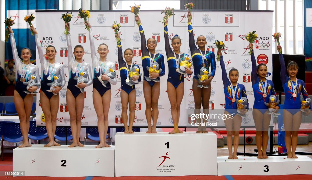 Team Brazil (C), Team Argentina (L) and Team Colombia (R) pose for a picturein the podium of Women's Team all-around as part of the I ODESUR South American Youth Games at Coliseo Miguel Grau on September 23, 2013 in Lima, Peru.