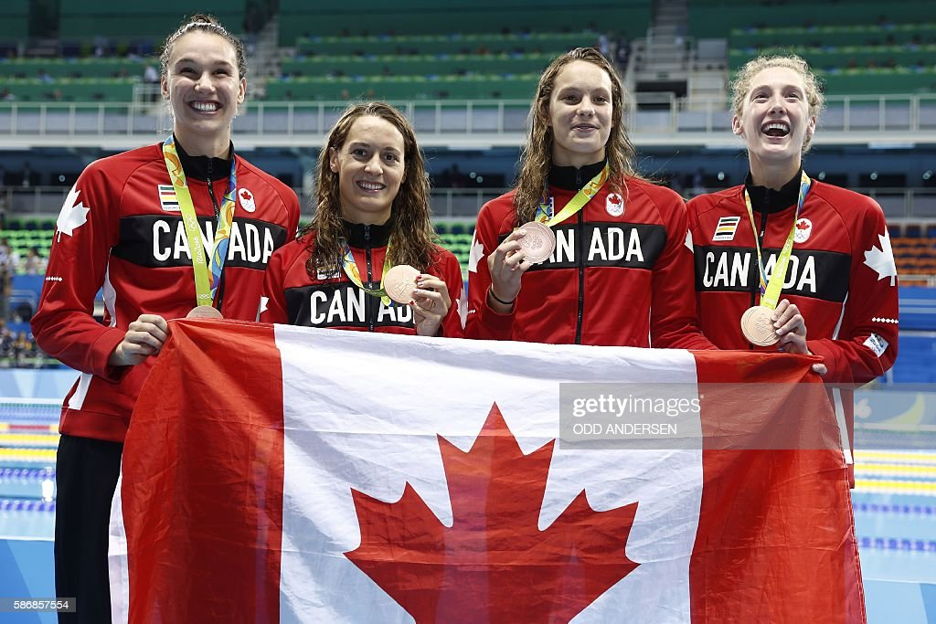 Team Canada, Canada's Sandrine Mainville, Canada's Chantal van Landeghem, Canada's Taylor Ruck and Canada's Penny Oleksiak pose with their bronze medals on the podium of the Women's 4 x 100m Freestyle Relay Final during the swimming event at the Rio 2016 Olympic Games at the Olympic Aquatics Stadium in Rio de Janeiro on August 6, 2016. / AFP / Odd ANDERSEN