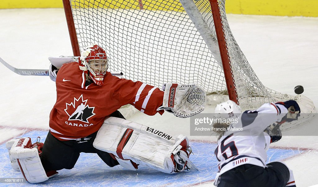 TORONTO, ON - DECEMBER 30 - Team Canada goalie Genevieve Lacasse (L) reaches to cover the net against Team United States Alex Carpenter (25) in first period exhibition Women's Hockey at the Air Canada Centre, December 30, 2013.