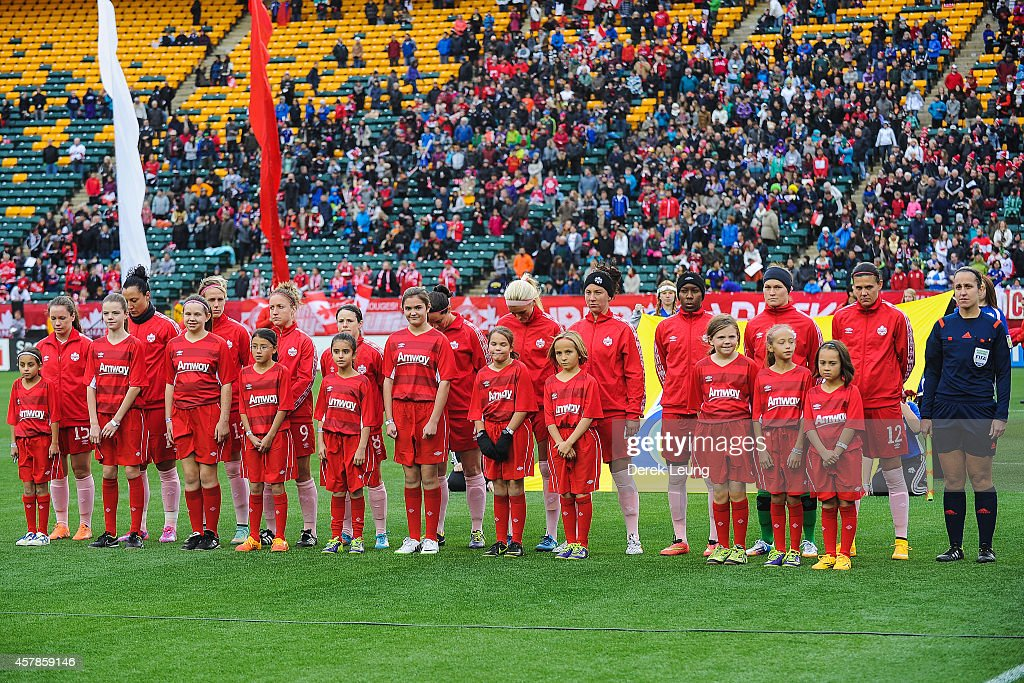 Team Canada lines up with kids during the singing of the national anthem prior to a match against Japan at Commonwealth Stadium on October 25, 2014 in Edmonton, Alberta, Canada.