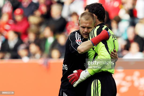 Team captain Andreas Wolf of Nuernberg hugs goalkeeper Raphael Schaefer to celebrate their team's first goal by team mate Ilkay Guendogan during the...