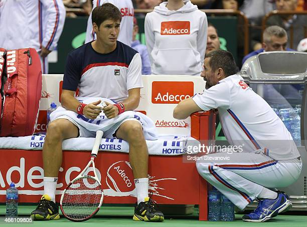 Team captain Bogdan Obradovic gives instruction to Dusan Lajovic during the match against Stanislas Wawrinka of Switzerland during day one of the...
