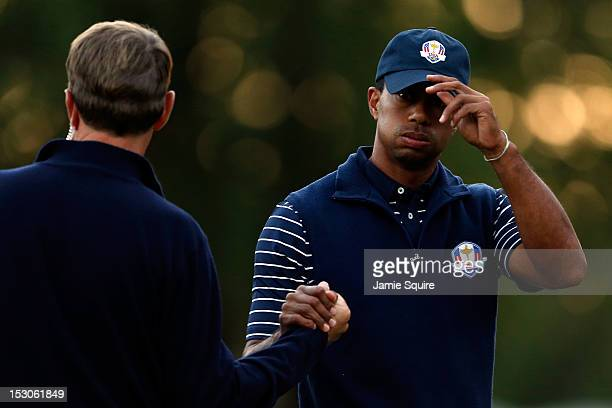 USA team captain Davis Love III greets Tiger Woods on the 18th green during day two of the Afternoon FourBall Matches for The 39th Ryder Cup at...
