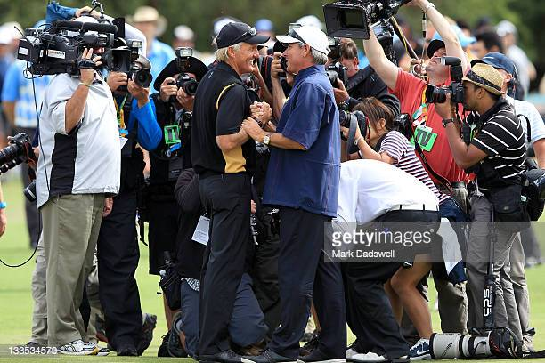 S Team captain Fred Couples shakes hands with International team captain Greg Norman on the 17th hole after the Day Four Singles Matches of the 2011...