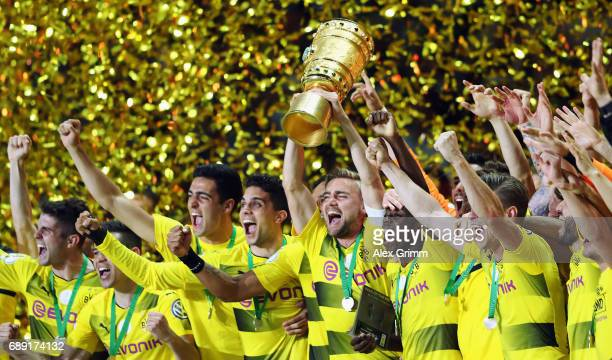 Team captain Marcel Schmelzer of Dortmund lifts the trophy after winning the DFB Cup Final between Eintracht Frankfurt and Borussia Dortmund at...