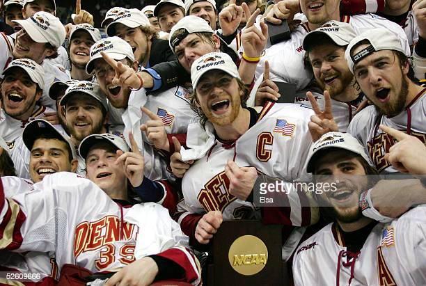 Team captain Matt Laatsch of the Denver Pioneers poses with teammates and the championship trophy after their victory over the North Dakota Fighting...